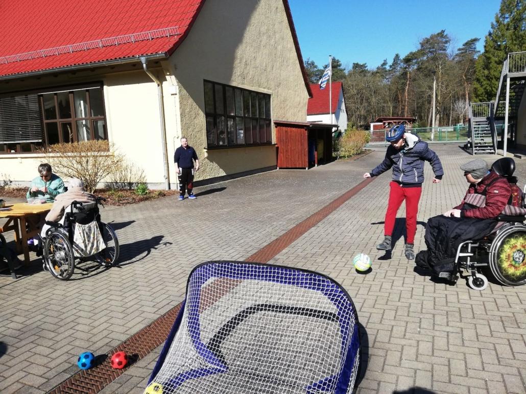 Ein junger Mann hat einen Fußball auf das Fußballtor geschossen, das etwa drei Meter entfernt ist. Ein anderer im Rollstuhl sieht aufmerksam zu.