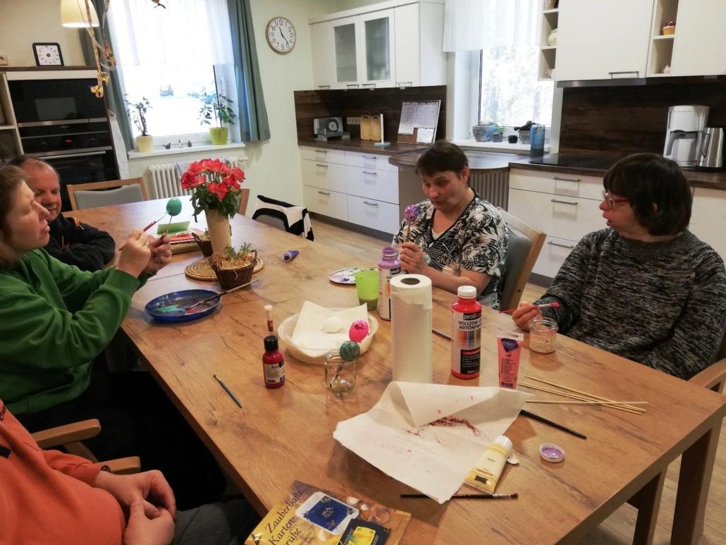 An einem großen Holztisch sitzen drei Frauen und ein Mann. Sie bemalen Ostereier mit verschiedenen Farben, z. B. Grün oder Violett.