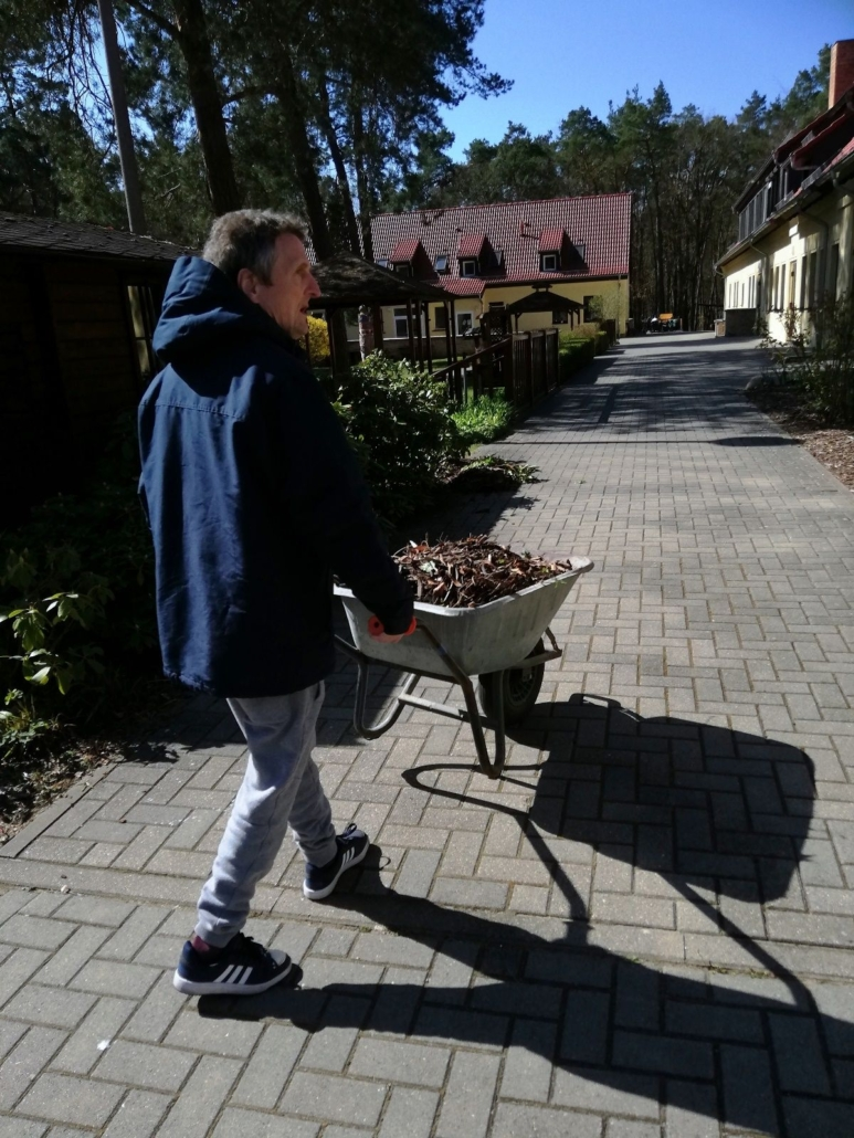 Ein Mann mit blauer Kapuzenjacke transportiert in einer Schubkarre Rindenmulch.