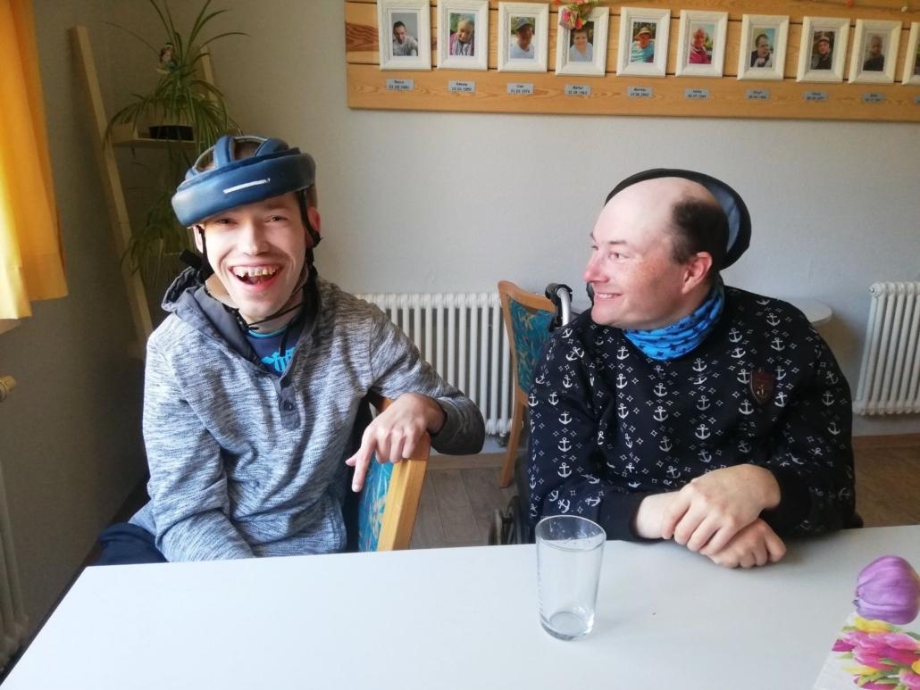 Zwei Männer sitzen lachend an einm Tisch. Dabei sitzt einer im Rollstuhl und hat sich seinem Nachbarn zugewandt.