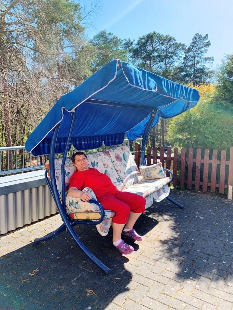 Eine Bewohnerin der Wohnstätte sitzt lächelnd auf einer blauen Hollywoodschaukel in der Sonne.