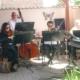 Eine Musikerin und drei Musiker sitzen unter einem Holzpavillon. Zwei von ihnen spielen Violine, einer Kontrabass und einer Trommel. Ganz rechts steht noch ein Keyboard. Vom Musiker sind nur die Hände zu sehen.