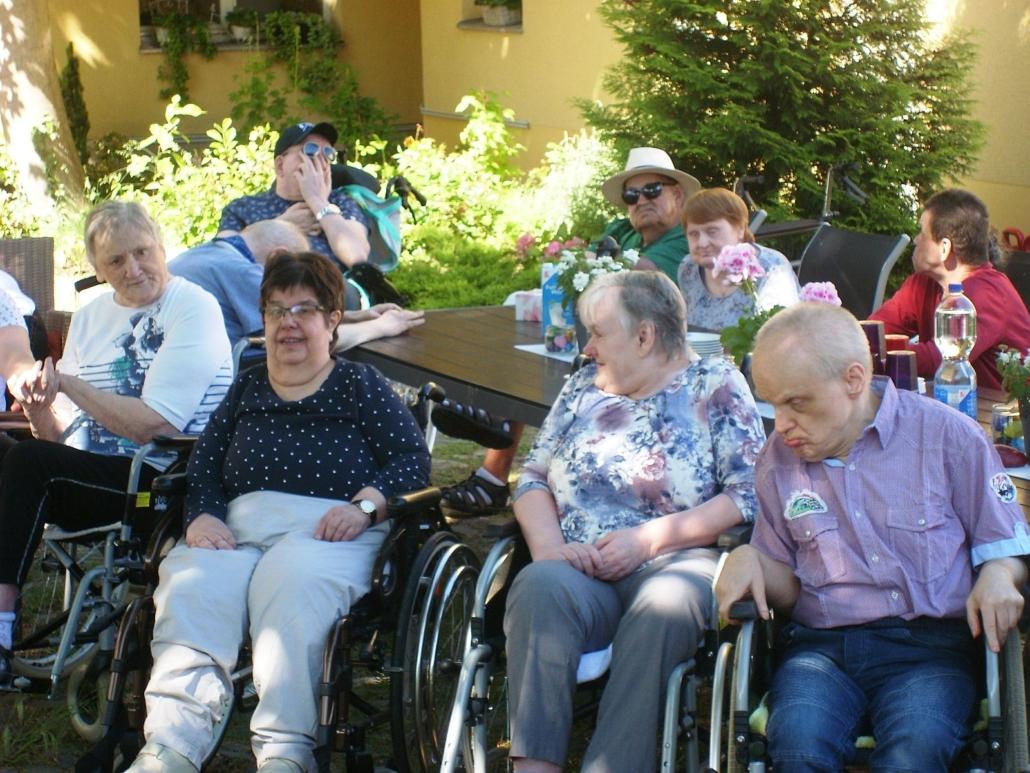 Die Bewohner sitzen im Innenhof mit dem Gesicht zum Konzertorchester. Ganz vorn stehen vier Rollstuhlfahrer