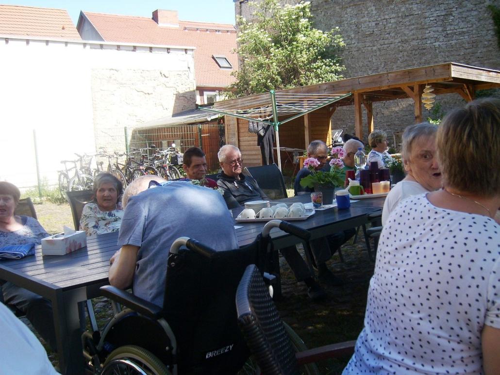 Das Konzert ist beendet. Die Bewohner sitzen an einer langen Tafel aus mehreren Holztischen. Darauf stehen Tassen, Teller und Trinkbecher.