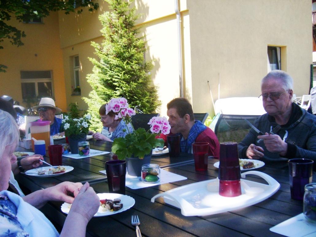 Die Bewohner sitzen im Innenhof an einer langen Tafel aus mehreren Holztischen. Sie essen gegrillte Bratwurst.
