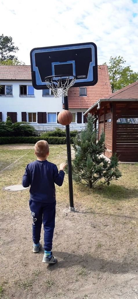 Ein junge steht in etwa 2 Metern Abstand vor einem Basketball-Korb. Er hat den Ball bereits geworfen.