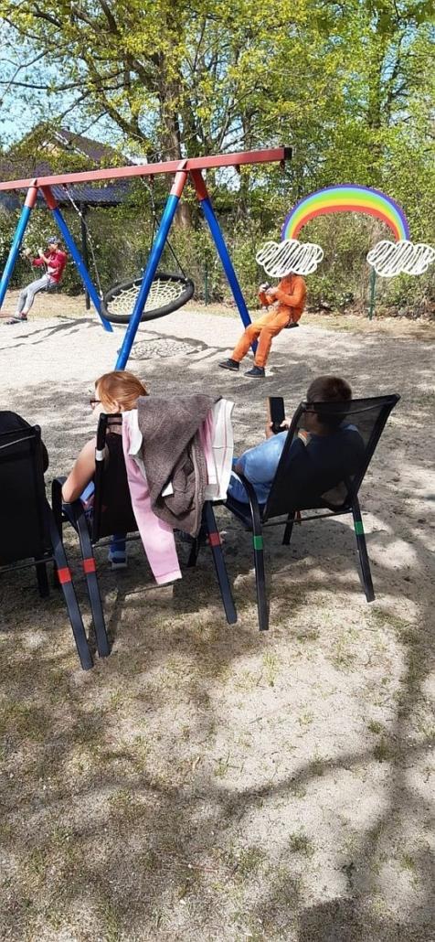 Im Vordergrund sitzen zwei Jugendliche auf modernen Gartenstühle in der Sonne. Einer beschäftigt sich mit seinem Handy. Im Hintergrund schaukeln zwei Mädchen.