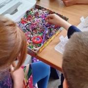 Zwei Mädchen und ein Junge sitzen am Tisch und basteln bunte Bänder. Zwischen ihnen steht ein Karton mit vielen Einzelteilen.