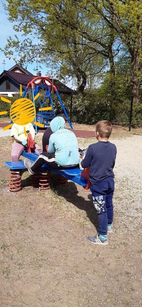 Zwei Kinder sitzen auf einer blauen Wippe. Auf der rechten Seite steht ein Junge am Ende der Wippe.