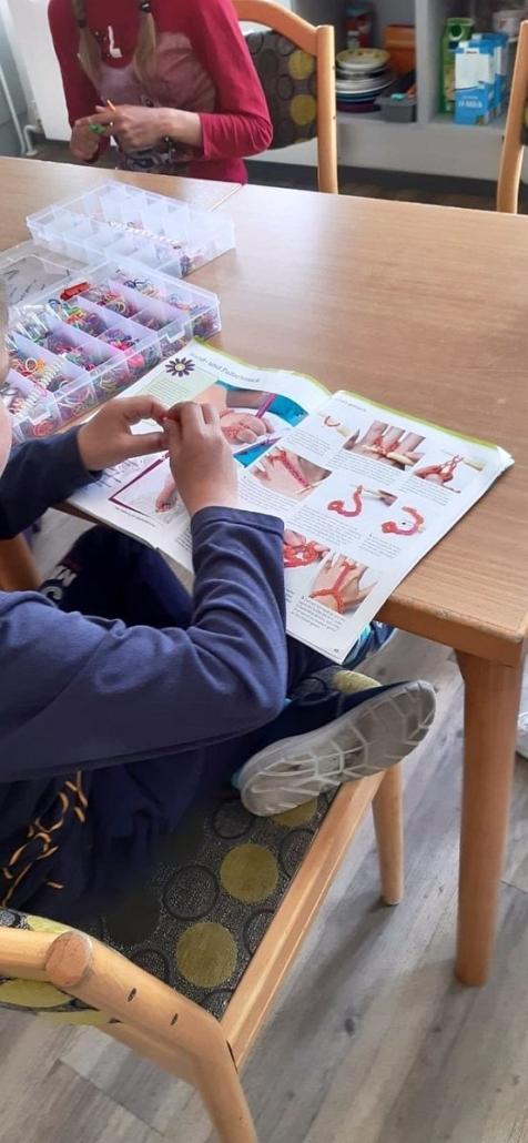 Ein Junge sitzt mit übergeschlagenem Bein am Tisch. Darauf liegt eine Anleitung zum Basteln von Hand- und Fuß-Schmuck.