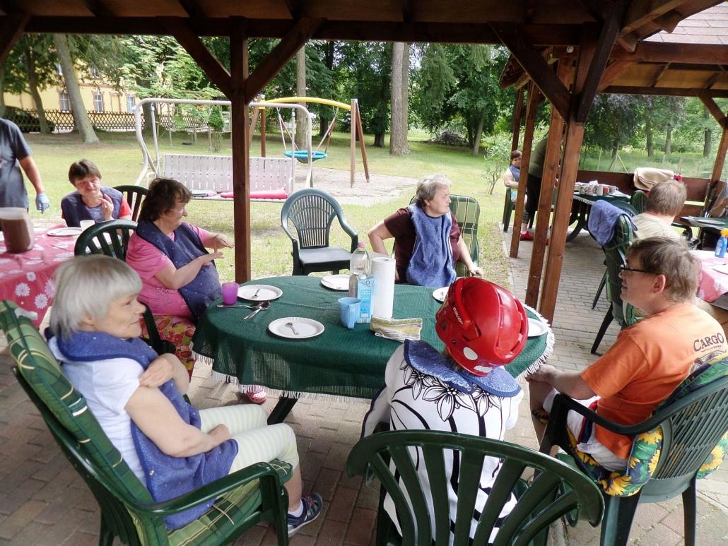 Unter Holzpavillons sitzen die Bewohner an verschiedenen Tischen. Vor ihnen steht Kaffeegeschirr. Im Hintergrund sind eine Hollywood-Schaukel und eine Nest-Schaukel zu sehen.