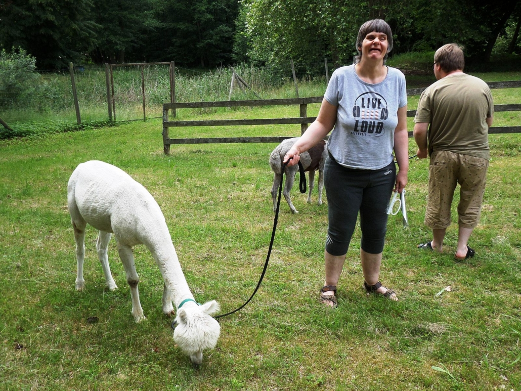 Eine Bewohnerin blickt in die Kamera. In der rechten Hand hält sie die Leine mit dem weißen Alpaka, das gerade Gras frisst. Im Hintergrund hat ein anderer Bewohner das graue Alpaka an der Leine, das ebenfalls grast.