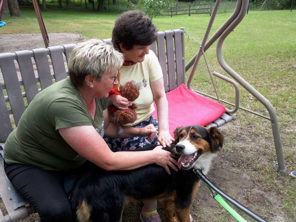 Eine Bewohnerin sitzt mit ihrer Betreuerin auf der Hollywood-Schaukel. Beide streicheln den Hund Cookie.