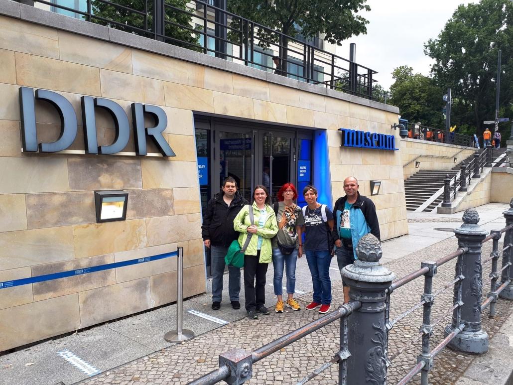 Eine Gruppe von drei Frauen und zwei Männers steht am Eingang des DDR Museums in Berlin. Das Gebäude hat eine Fassade aus hellem Sandstein.