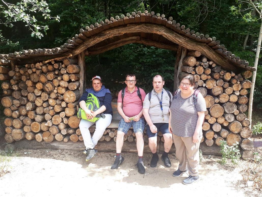 Drei jung Männer sitzen auf einer Holzbank die auf gestapelten Holstämmen befestigt ist. Sie hat ein Dach aus dünnen Holstämmen und Seitenwände aus gestapeltem Holz. Rechts neben den Männern steht eine Frau mit gestreiftem T-Shirt.