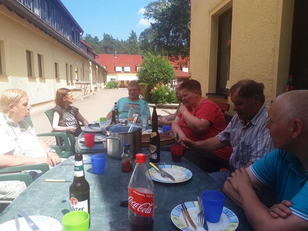 Auf dem Hof der Wohnstätte Sonnenhof sitzt eine Gruppen von vier Frauen und drei Männern an zwei nebeneinander stehenden Tischen und sind fas fertig mit dem Essen.