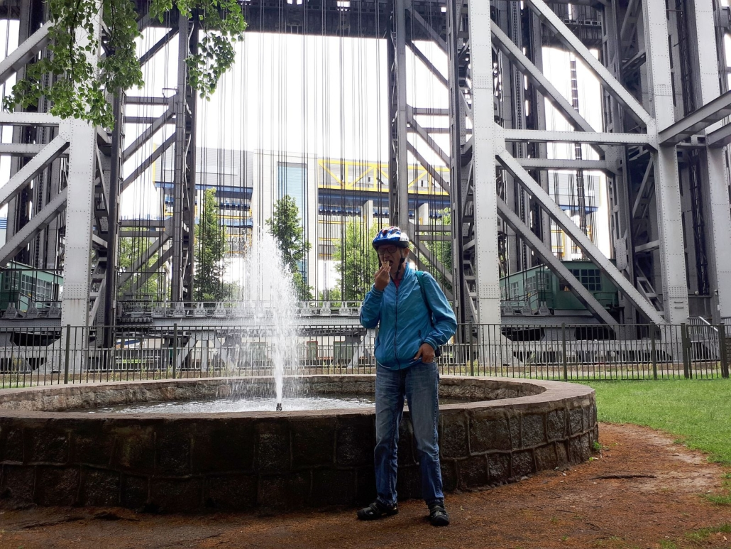 Ein junger Mann mit Fahrradhelm steht vor einem Springbrunnen und isst ein Eis. Im Hintergrund sind das alte und neue Schiffshebewerk zu sehen.
