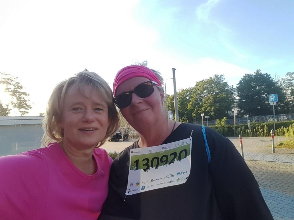 Frau Bester und ihre Begleiterin Anja lächeln nach 6,5 km Walking in die Kamera. Frau Bester hat ein pinkfarbenes Stirnband und die Startnummer um.