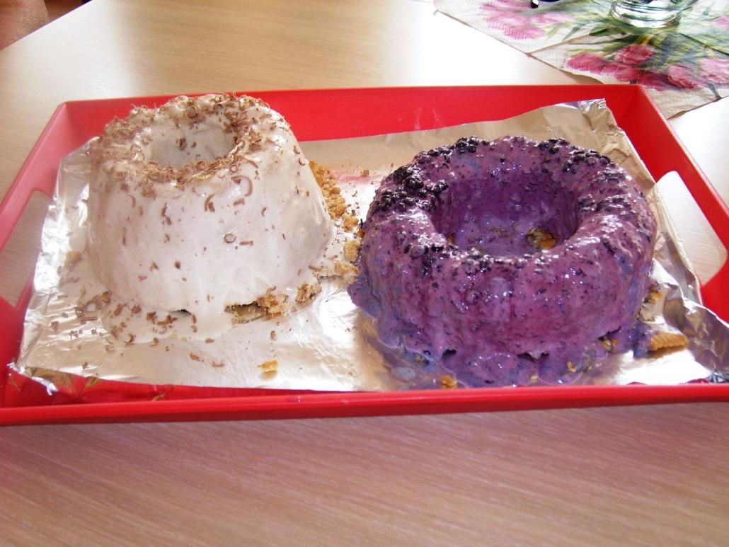 Ein weißer und ein violetter Gugelhupf aus Eiscreme liegen in einer flachen, roten Schale.