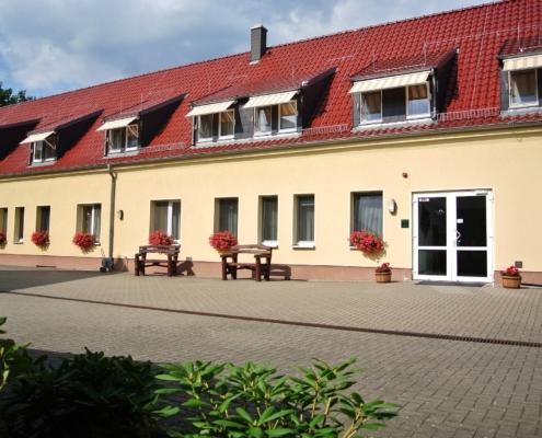 Das Gebäude des Sonenhofes ist gelb und besteht aus Erd- und ausgebautem Dachgeschoss mit Dachgauben. Auf den Fensterbretern stehen Balkonkästen mt roten Geranien. Davor sind Holzbänke aufgestellt.