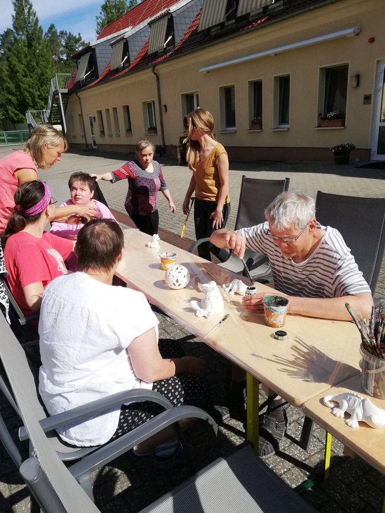 An einem langen Tisch aus Bierzeltgarnituren sitzen Bewohner des Sonnenhofes und beginnen verschiedene weiße Keramitkfiguren zu bemahlen. Darunter sind Katzen in verschiedenen Größen.