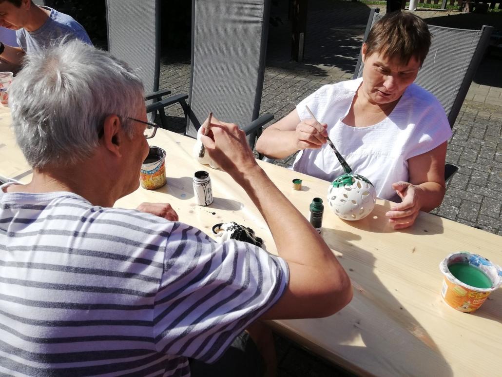 Eine Frau malt eine durchbrochene Keramikkugel grün an. Der Mann ihr gegenüber bemalt seine Figur schwarz.