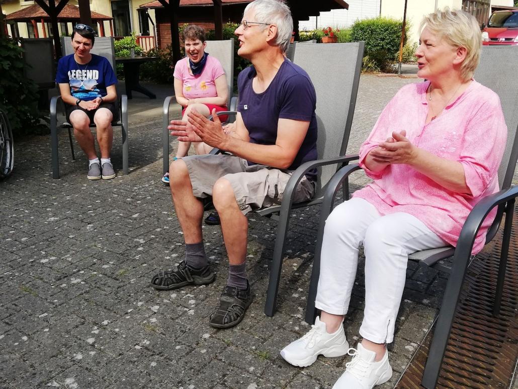 Vier Zuhörer, zwei Frauen und zwei Männer, sitzen auf grauen Gartenstühlen mit hoher Lehne. Sie freuen sich und klatschen.