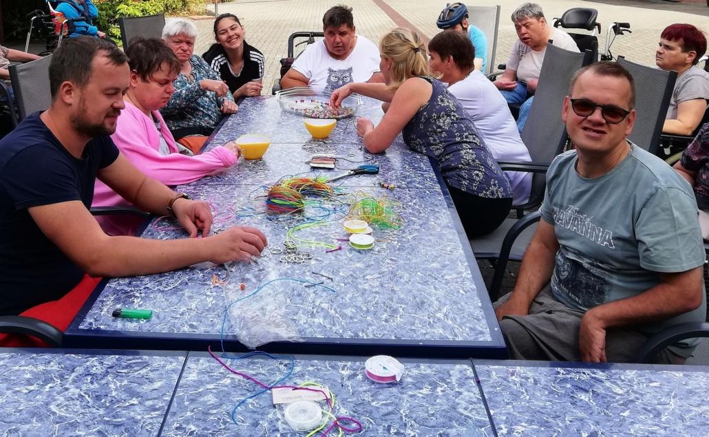 Die Bewohner des Sonnenhofes sitzen an großen, grauen Tischen. Darauf liegen verschiedenen Bastelmaterialien wie Perlen, Bänder und Scheren.