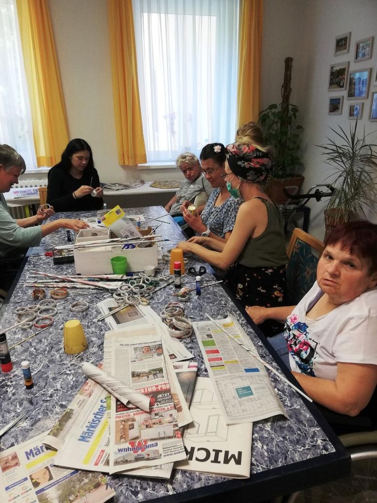 Um einen grau marmorierten Tisch sitzen sechs Frauen. Auf dem Tisch liegen alte Zeitungen und verschiedene Bastelmaterialien.