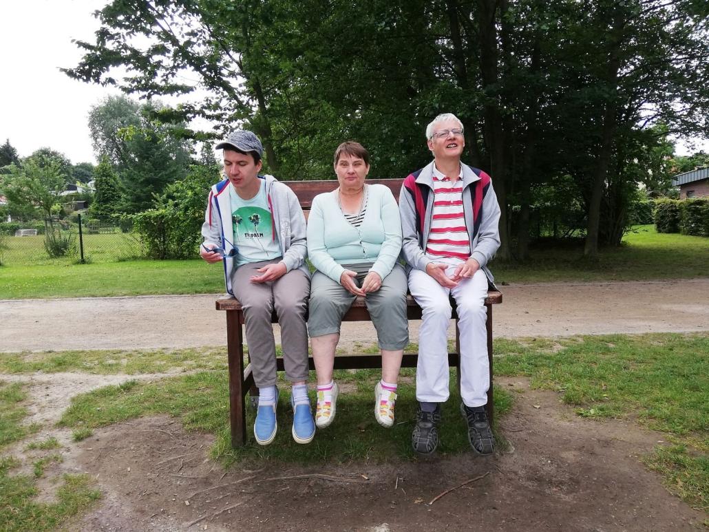Am Rande eines Weges sitzt eine junge Frau auf einer braunen Holzbank zwischen zwei Männern. Im Hintergrund sind Bäume am Rande einer Wiese zu sehen.