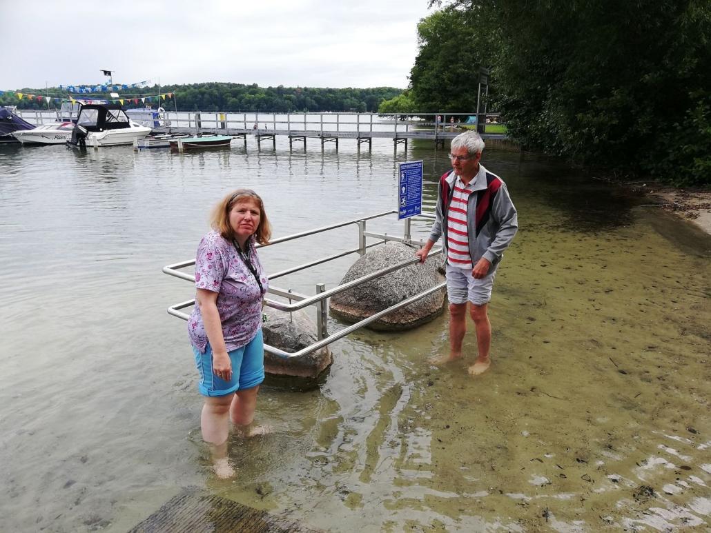 Mit den Füßen im Wasser des Werbellinsees fassen eine Frau und ein Mann an einem Edelstahlgeländer an. Das ist auf zwei großen Findlingen montiert und gehört zur Kneip-Anlage.