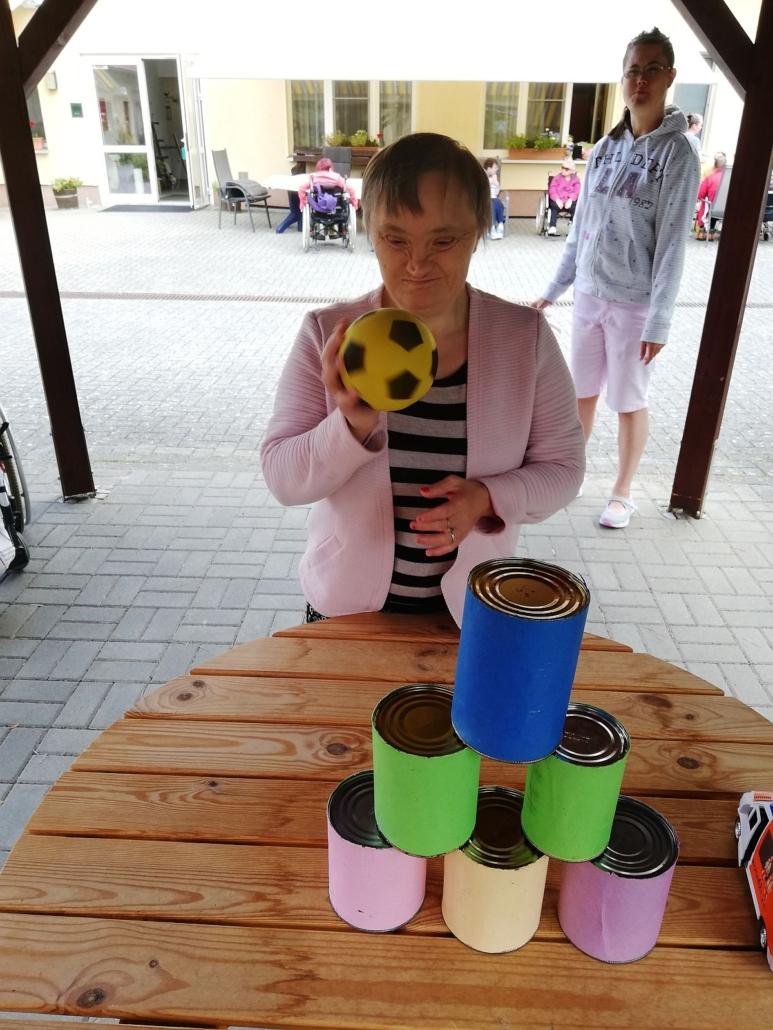 Eine junge Frau mit einem rosa Blazer hat einen schwarz-gelben Ball in der Hand. Sie zielt auf die bunten Büchsen, die vor ihr auf dem Tisch stehen.