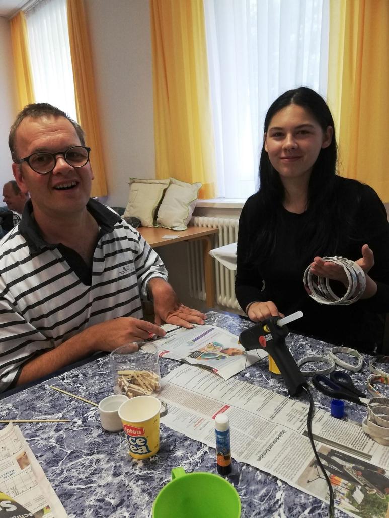 Ein junger Mann faltet Zeitungspapier. Die junge Frau neben ihm hält mehre fertige Ringe aus Zeitungspapier in ihrer linken Hand. Beide lächeln. Vor ihnen steht eine KLebepistole.