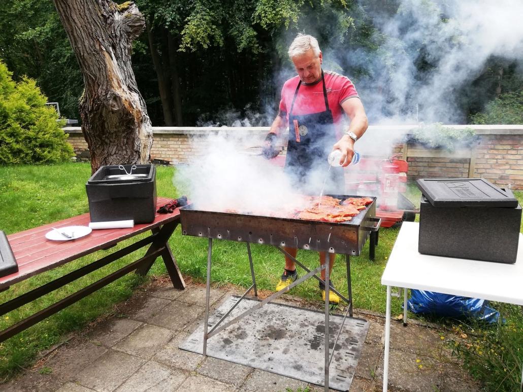 Der Hausmeister der Wohnstätte Sonnenhof steht am dampfenden Grill. Er löscht das Fleisch gerade mit Wasser ab.