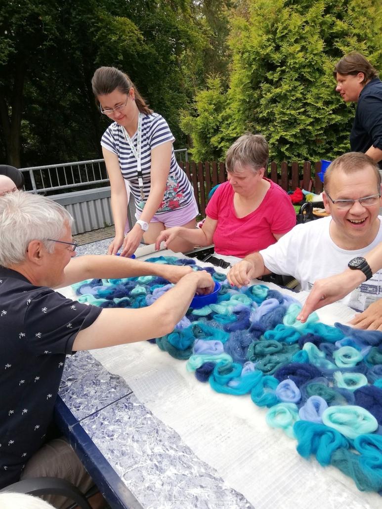 Auf dem Tisch liegt ein langer, breiter Streifen blauer Filz-Wolle in unterschiedlichen Farbtönen. Mehre Bewohner feuchten diese gemeinsam an.