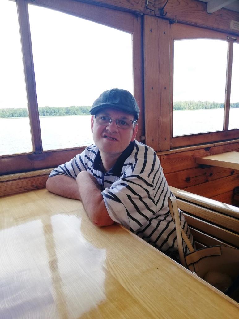 """Im Unterdeck der """"Altwarp"""" sitzt ein junger Mann mit blauem Basecup und gestreiftem T-Shirt allein an einem Tisch."""