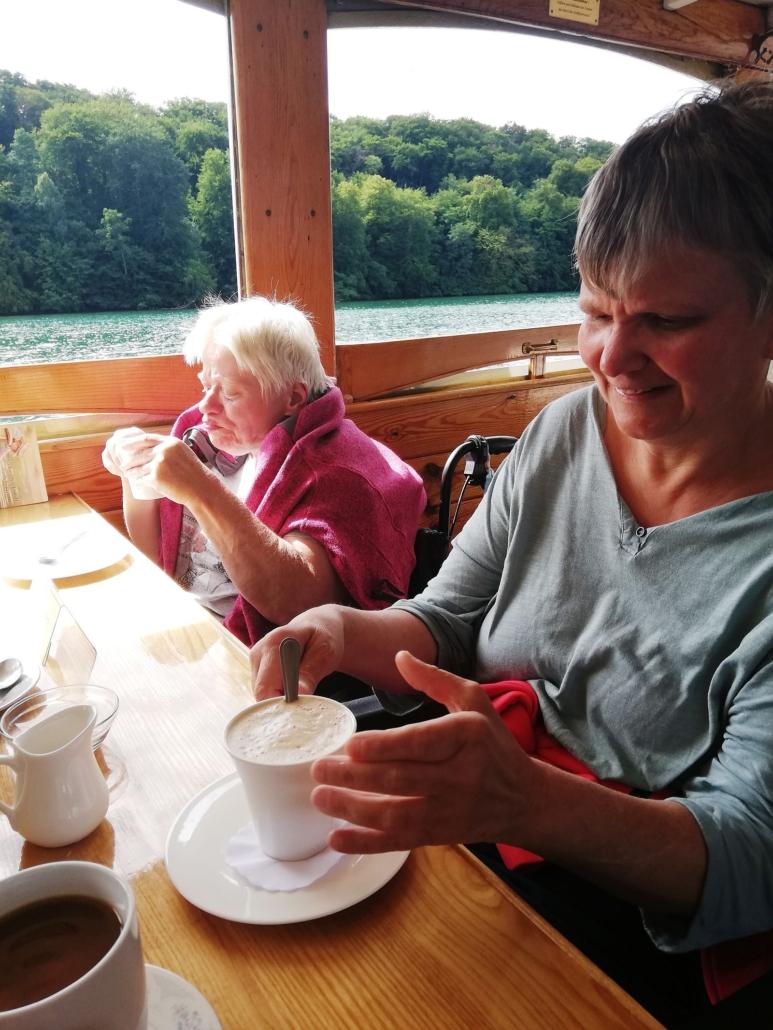 """Zwei Frauen sitzen an einem Holztisch im Innendeck des Schiffes """"Altwarp"""". Sie trinken Kaffee."""