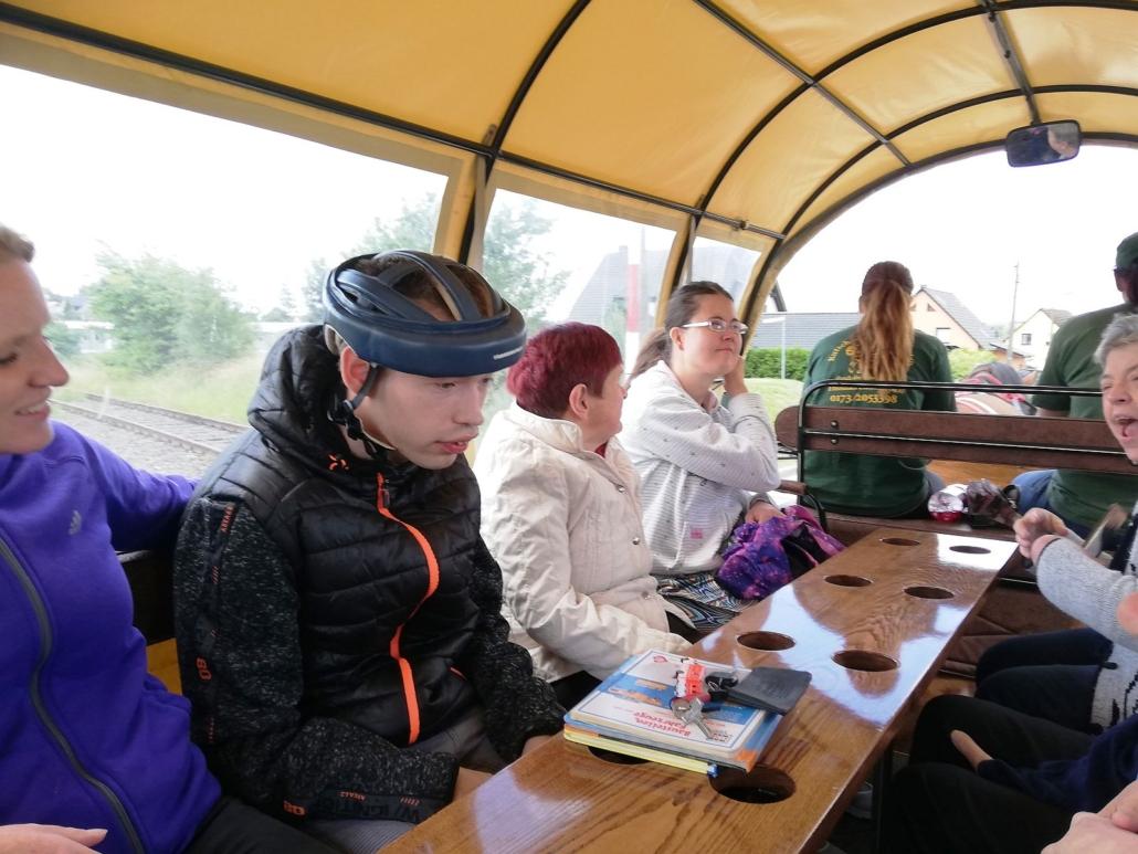 Hinten auf dem Kremserwagen sind insgesamt sechs Personen zu sehen. zwischen ihnen befindet sich eine schmale Tischplatte mit runden Ausschnitten für Getränke.
