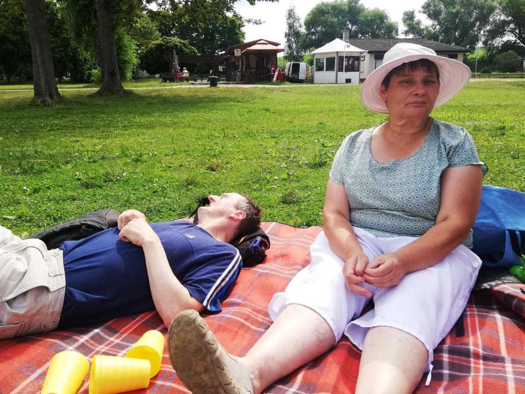 Auf einer orangen Decke liegt ein Mann mit blauem T-Shirt. Daneben sitzt eine Frau mit grünem Oberteil. weißer Hse und Sonnenhut.