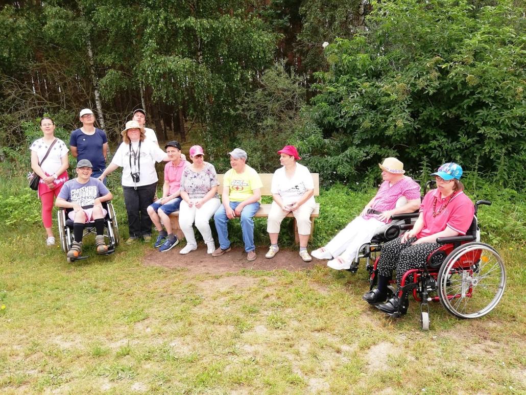 Am Waldrand macht die Gruppen aus sechs Frauen und fünf Männern eine kurze Verschnaufpause. Drei von ihnen sitzen im Rollstuhl und vier weiter haben auf einer Bank Platz genommen.
