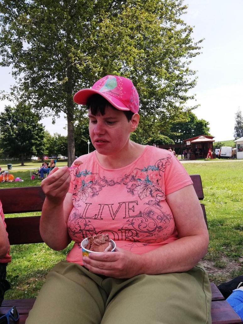 Eine junge Frau mit rosa T-Schirt und pinkem Basecap sitzt auf einer braunen Holzbank. Sie isst ein Schokoladeneis aus einem Becher.