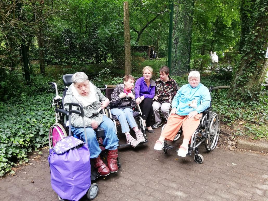 Am Rande des Weges stehen drei Rollstuhlfahrerinnen. Dahinter sitzen zwei Frauen auf einer Bank. Der Boden ist feucht. Die Menschen haben Jacken an.