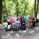 Die Gruppe hat sich am Rande eines Geheges, das teilweise mit Bäumen bewachsen ist, zum Gruppenfoto aufgestellt. Vorn stehen drei Rollstuhlfahrer und eine Person mit Rollator. Dahinter stehen die sieben anderen Teilnehmer.
