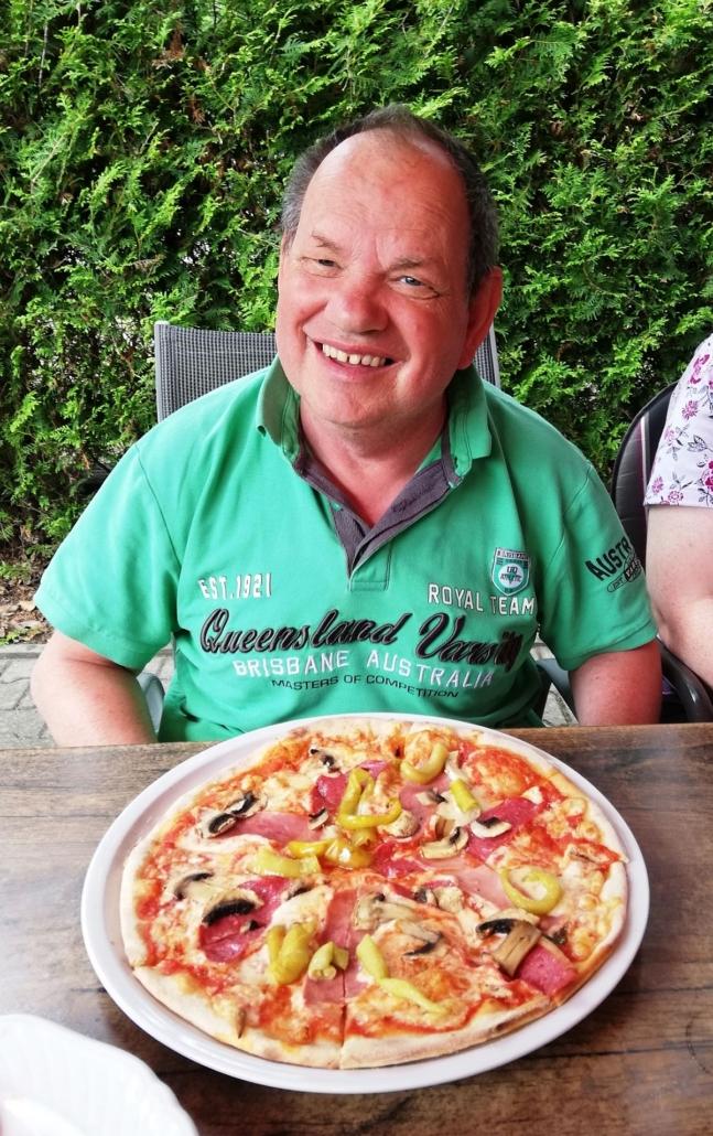 Ein Mann mit grünem Polo-Shirt strahlt über das ganze Gesicht. Vor ihm auf dem Tisch steht eine große, leckere Pizza, unter andere, mit Schinken, Peperoni und Champignons.