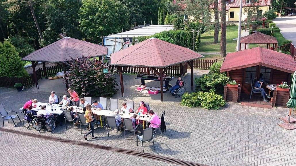 """Ein Blick von oben auf das Gelände der Wohnstätte """"Sonnenhof"""". Links im Vordergrund steht der lange Tisch mit der Keramik, um den insgesamt 14 Personen versammelt sind. Dahinter stehe Holzpavillons. Davon sind zwei mit jeweils einer Person besetzt."""
