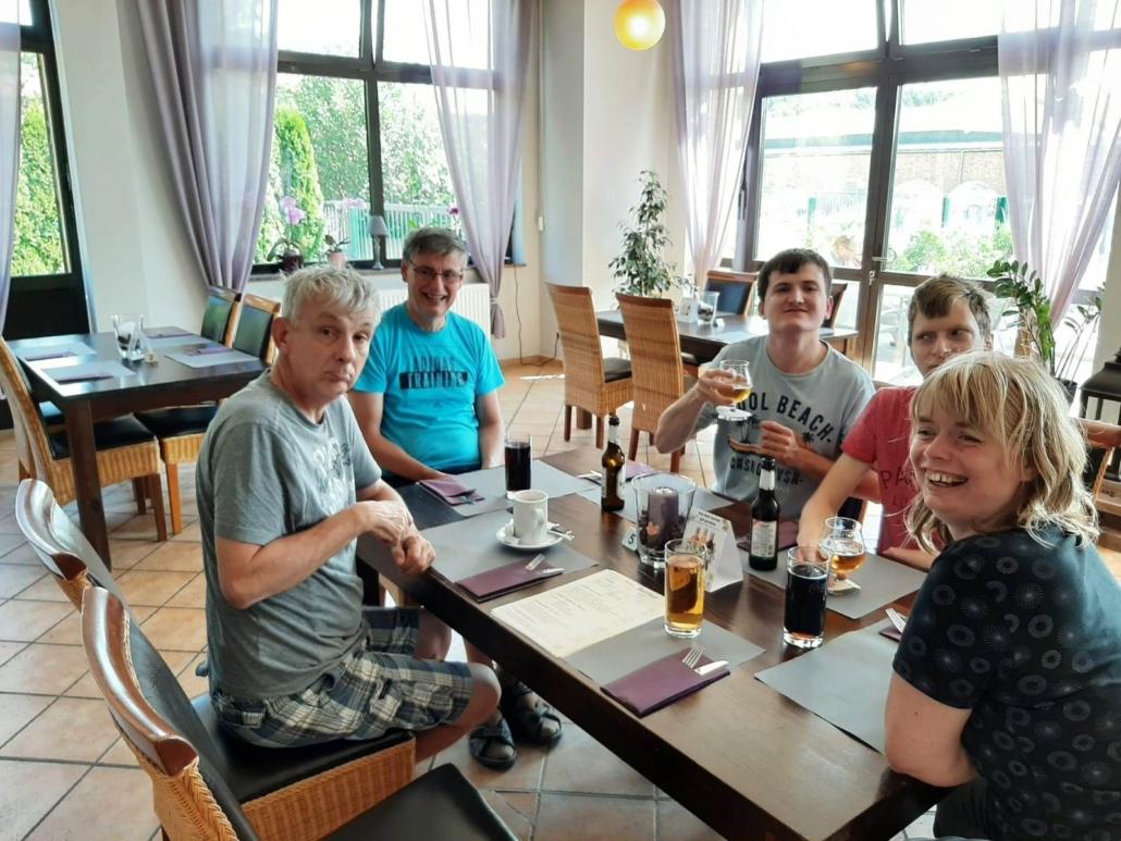 Die Fünfer-Gruppe sitzt um eine viereckigen, dunkelbraunen Holztisch. Vor ihnen stehen verschiedene Getränke. Einer hebt sein Glas in Richtung Kamera.