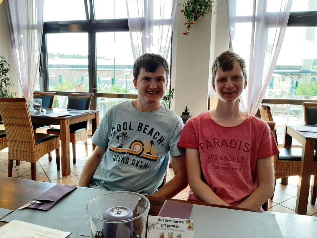 Zwei Männer sitzen am Tisch in Anna´s Gasthaus und blicken freundlich in die Kamera. Auf dem Tisch liegen Bestecktaschen und in der Mitte steht ein Windlicht mit violetter Kerze.