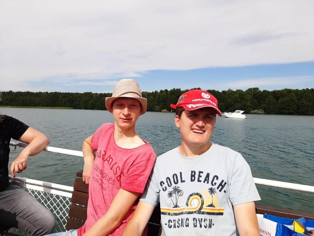 Zwei junge Männer sitzen an der Reling des Schiffes und blinzeln gegen die Sonne in die Kamera. Weit hinter ihnen ankert ein weißes Motorboot vor dem bewaldeten Ufer.