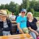 """Auf dem Oberdeck der """"Altwarp"""" sitzen drei der Ausflügler ,eine Frau und zwei Männer, auf einer dunkelbraunen Holzbank an einem Tisch. Der eine Mann hat seine linken Arm um die Freu gelegt. Das Paar lacht in die Kamera. Im Hintergrund ist das von Bäumen bestandene Ufer zu sehen."""