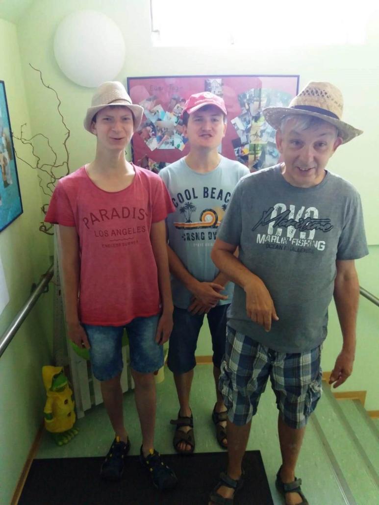 Drei Bewohner des Heidehauses stehen auf einem Treppenabsatz. Alle drei haben kurze Hosen und T-Shirts an. Auf dem Kopf tragen sie Strohhüte bzw. ein Basecap.